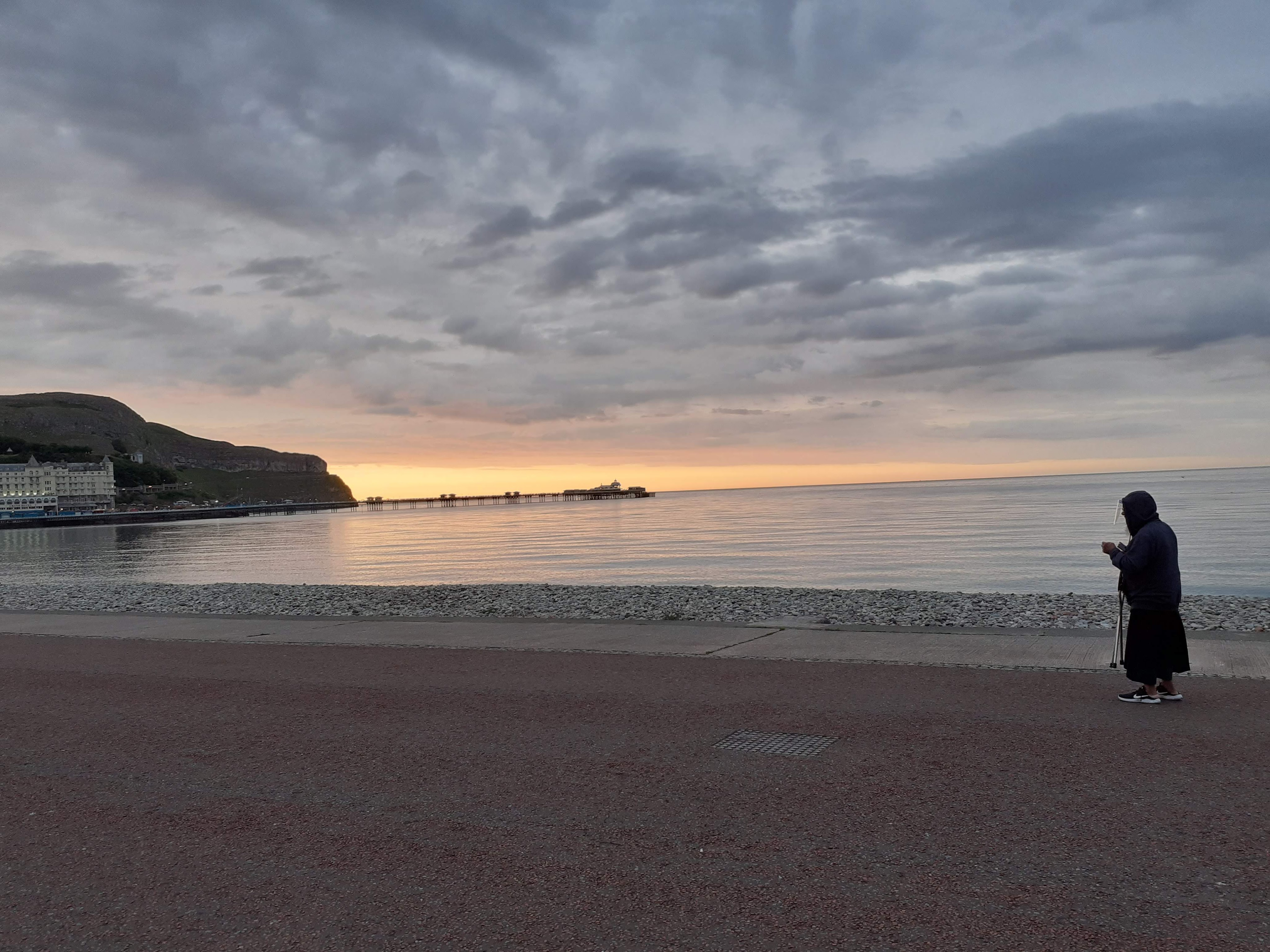 Sunset over Llandudno Pier. A man in shadow in hoodie and mask looks almost like a monk.