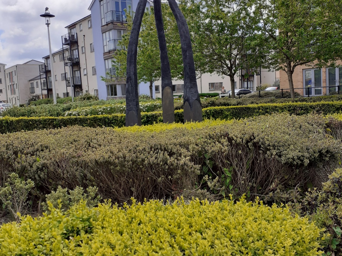The photo shows a sculpture of three burnt matchsticks in portishead
